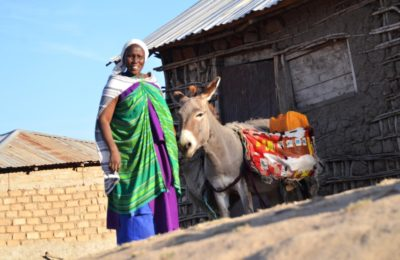Sabina with a donkey in front of her house